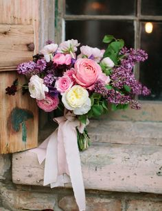 stunning purple bouquet featuring garden roses, ranunculus and lilacs by Abany Bauer