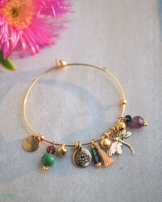 The Dragonfly bangle is inspired by the graceful dragonfly, which has flown the earth for over 300 million years, and the beautiful lotus flower which grows through mud and slime in order to bloom. The bangle features a 22k gold plated dragonfly and lotus charms, which serve to remind us to rise above obstacles, overcome hardships and achieve the impossible. The bangle also includes Turquoise and Amethyst stone beads on a 22k gold plated open-close bangle.