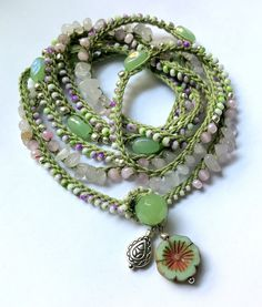 Pretty, one of a kind crochet beaded necklace or wrap bracelet featuring Czech fire polished faceted beads and seed beads in several lovely shades and textures of olive, pink, lilac, and silver crocheted on to soft crochet thread in flax. This lovely piece measures approx. 50 (127) and can be worn as a single, double or triple strand necklace or wrapped as a bracelet about 7x on a 6 - 6.5 wrist. Fastens with loop and glass ball bead. Check out more necklaces here: https://www.etsy....