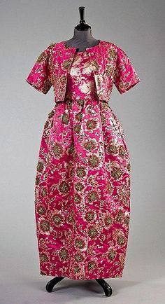 A Balenciaga couture shocking pink and gold brocade evening gown and bolero jacket, Spring-Summer, 1964, labelled and numbered 92586, the skirt and bodice emblazoned with gold and silver beaded starbursts outlined in rose chenille, the jacket with three domed silk covered buttons, bust 82cm, 32cm, waist 61cm, 24in, (2)