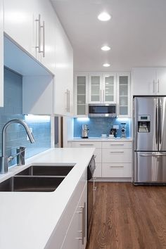 Kitchen with white painted, flat panel, custom cabinets and white quartz countertops - Appliance & Fridge Wall. Pinned by #ChiRenovation - www.chirenovation.com