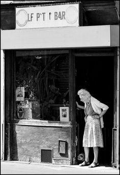 Le piéton de Charonne » Paris – 11ème arrondissement – Wahou et sa maîtresse. Le P'tit bar c'est presque une institution. En fin de matinée, madame Paulo monte le rideau de fer, ramasse les sacs de pain laissés par les voisins et commence par nourrir les pigeons... . Le matou d'aujourd'hui, bien que très âgé, a conservé son instinct de chasseur et c'est bien attaché à sa longe qu'il surveille le repas des bisets.