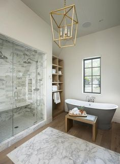 A Darlana 4 Light Lantern hangs from a sloped shiplap ceiling over white marble accent tiles framed by pine wood floors in this chic gray and white transitional bathroom.