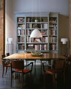 Wood floor + grey walls + wood table + leather chairs + white light fixture + grey shelves + books = the dining room