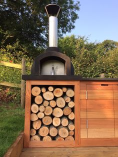 A great close up shot of a custom made pizza oven with the oven sitting on a slate work surface in a solid wood unit below.