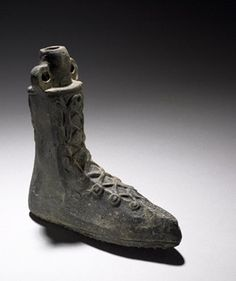 Imperial Rome. 1st-2nd century. Terracotta scent bottle in the form of a boot laced up at the front. On the bottom the nails are arranged in the form of a swastika and the Greek letters alpha and omega.