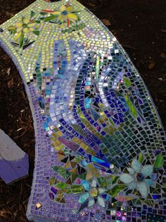 Sun/moon mosaicked concrete garden bench using scrap glass and broken fused tiles.