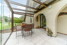 Our paving creates clean lines that look striking against the archways of this home. Glass Room, Glass Garden, South Wales, Porcelain Tile, Clean Lines, Case Study, Concrete, Pergola, Tiles