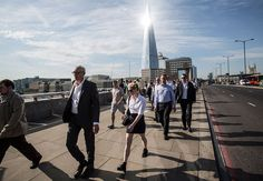 Commuters make their way to work across London Bridge, with the sun reflecting from the Shard, London's tallest building