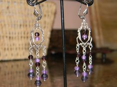 """Victorian Reproduction stamping layered in oxidized sterling silver. Suspended are genuine Amethyst & Garnet, along with sparkling crystals for extra pizazz! 3"""" long. $12"""