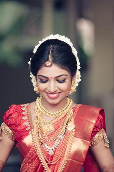 South Indian Brides - Rose and Gold Kanjivaram Sari | WedMeGood Bright Red Puff Sleeves Blouse and a rose and gold kanjivaram sari, Gold layered jewelry with gold borla and gajra bun #wedmegood #gajra #gold #kanjivaram