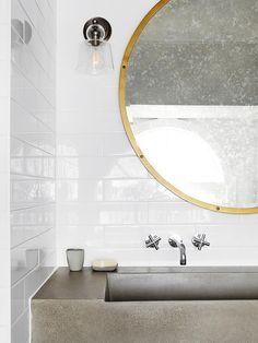 banheiro com bancada de cimento parede de cerâmica branca e espelho circular