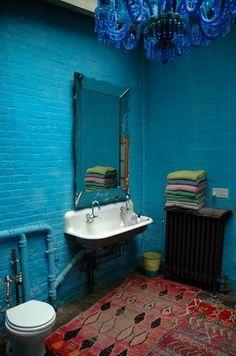 Blue painted brick in the bathroom with the Kohler Brockway sink