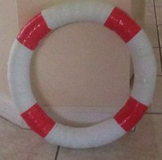 Made my own life preservers☺️.  Pool noodle purchased at Dollar Tree folded into a circle taped ends together, then wrapped pool noodle with white streamer also purchased at Dollar Tree, then used red masking tape to create stripes