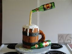 I used two metal coat hangers, and bent them in a circle on one end and taped them underneath the base of the cake. I ran the tape straight up to the point where it bends to the fit the beer bottle over top at an angle. Then I took my four stacked six inch frosted round cakes ; then cut half way through on one side, then slid all four cakes around the coat hanger. Then I glued on the stiff fondant painted with wood grain