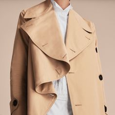 A weatherproof cotton gabardine coat artfully draped on one side of the closure, inspired by the fluid lines and curves of Henry Moore's sculptures. The gently A-line silhouette is finished with a deep back vent.