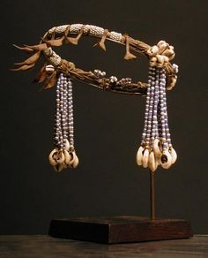 Kirdi Beaded Crown. A number of divers ethnic groups cumulatively described as Kirdi live in the rugged mountains of northeast Cameroon. They are farmers who adhere to traditional beliefs, initiating their youth to adulthood and celebrating their harvest with ceremonies and dances. This crown is worn by young women during one such ceremony. In addition to glass trade beads and imported cowrie shells the crown features a line of ersatz lion claws locally fabricated by a blacksmith from raw…
