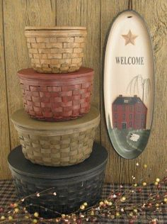 Prim welcome sign with saltbox and a pile of baskets