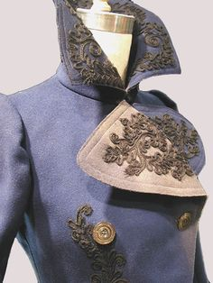 "Deep Royal Blue Jacket - double-breasted outer coat, c. 1900, Melton wool dyed deep royal blue. The outside of the coat is decorated with black cotton passementerie braid at the front lapels, around the collar edge, down center front, around the hem to the back. Center back has a large motif as well as do the lower edges of sleeve hems. There are two hand finished button holes 1 1/4"" wide with a set of four mother of pearl buttons that close the double breast."