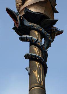 Poste de luz modernista, de Gaudí, en pl. Real, Barcelona. La parte superior es un casco que representa al Dios Mercurio, y las 2 serpientes que le siguen  hacen referencia a la leyenda de la mitología griega, donde Mercurio, al ver a dos  serpientes enfrentadas, logró separarlas pacíficamente utilizando sólo un bastón. Este es el símbolo de los negocios y el comercio, y dado que los postes de luz están en el antiguo centro comercial de la ciudad, el simbolismo cobra un sentido perfecto.