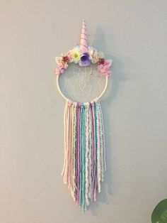 "Everyone's Crazy about Unciorns and Dreamcatchers! So why not have both!! Every little girl is sure to love this. It has been my most popular so far. Made with an 8"" hoop and is approx. 28"" long. Different colors and textures of fibre, ribbon and beads. Horn is pink fabric sewn and"