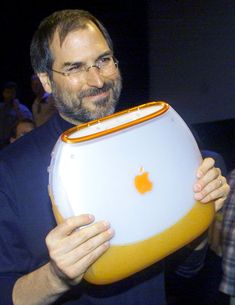 Apple Computer Chief Executive Steve Jobs poses with the company's new iBook portable computer at the MacWorld computer trade show in New York on July 21, 1999.