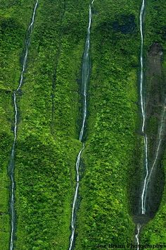 Deeply etched waterfalls lining the Waialeale crater walls. More waterfalls than we could count during helicopter tour.