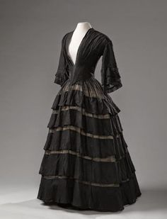 Black muslin dress, 1850-55 (Translated) Black wool muslin gown, with flared sleeves, tight fitting bodice and five strips (tiers) on the skirt. The bodice with V-neck runs from the front into a point and is lined. On the inside of the body (bodice) are the original waistbands. Along the bottom of the skirt a lace tape along the seam.