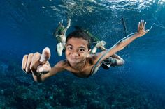 """A young village boy leaps from his dugout canoe and dives down to investigate me in my scuba gear, as I exhale bubbles and hold out my a huge underwater camera dome! The villagers are Alor, Indonesia continue to live off the sea, mostly fishing with hand-lines and handmade wooden fish traps. The joy and innocence of the children in these communities is inescapable."" Photo and caption by Shawn Heinrichs/National Geographic Photo Contest"
