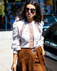 A lace-up blouse is worn with a suede wrap skirt.