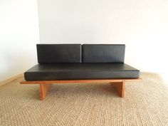 This black leather miniature daybed sofa has timeless style that would be suitable in a mid century or a contemporary setting. The base and legs are made