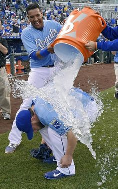 Kansas City Royals relief pitcher Greg Holland (56) gets the ice water cooling down from catcher Salvador Perez (13) and catcher Francisco Pena after the teams 7-3 win over the Cleveland Indians during Thursday's baseball game on May 7, 2015 at Kauffman Stadium in Kansas City, Mo. Holland made his first appearance after coming off the disabled list.