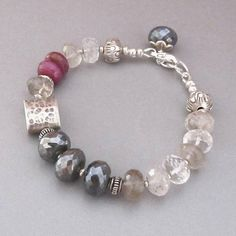 Gorgeous sparkling Rutilated Quartz alternated with tiny handmade silver beads mingle with Mystic Labradorites, Pink Sapphires and a handmade silver lotus beads and a box charm. It closes with a lobster claw clasp and an extender chain with another Mystic Labradorite capped in silver petals