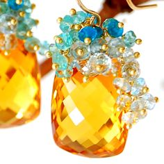 Aqua hued tendrils of blue topaz and apatite crown these dramatic and glamorous citrine earrings. Each of the blue gemstones is poised on artisanal Balinese 24 karat vermeil headpins, hand-linked, one by one, in dramatic contrast with the AAA flawless citrine cushion cut focal stones which total 44.50 carats and are custom cut for Amy Holton Designs. The pair is suspended from 14 karat gold-fill handcrafted ear wires (solid gold available on request, please contact for a quote).