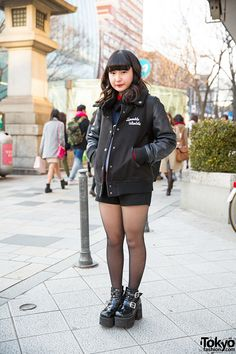 19-year-old Rina on the street in Harajuku wearing a stadium jacket with shorts, platform heels, and a Prada backpack.