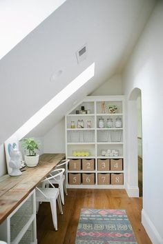 Craft room features a sloped ceiling fitted with skylights over a reclaimed wood plank desk lined with white metal chairs alongside a built-in bookcase filled with numbered bins.