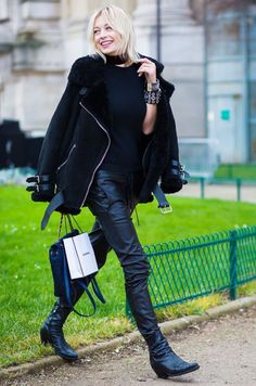 A black moto jacket is paired with black leather pants, black boots, and a Chanel bag
