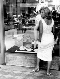Marilyn in fashion~ For a 1957 photo series of Marilyn exploring locations in Brooklyn and Manhattan, she chose this white cotton sundress. Though she is all in white, she's carrying a black clutch. This dress reportedly cost 5.98