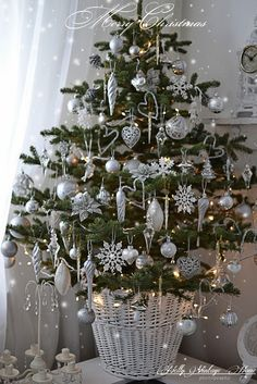 Pretty little tabletop Christmas tree inspiration. Small tree, white basket, silver and white ornaments, and a strand of clear Christmas lights.