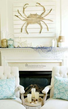 candels, blue pillows, fishing net, starfish, crab art, rope in vase, white vases, summer - coastal mantel