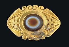 A ROMAN GOLD AND EYE AGATE FINGER RING   CIRCA 2ND-3RD CENTURY A.D.   The solid cast hoop flat on the interior, angled on the exterior, the outer edges of the lower portion of the hoop with a raised molding of scrolls expanding to openwork volutes, the triangular shoulders each decorated with a pierced-work vine leaf and tendrils, the outer edges of the oval bezel framed by pairs of volutes, set with a bevelled oval eye agate