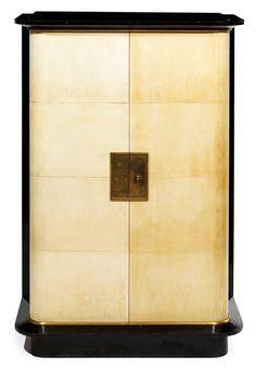 Jacques ADNET (1900-1984) Élégant meuble de rangement, 1937, à structure principale parallélépipédique en latté gainé de parchemin, soulignée en pourtour d'un jonc en bronze doré. Il repose sur une plinthe en retrait en bois noirci et verni, à l'instar de la corniche à large doucine en ressaut soulignant le corps gainé de parchemin Haut. 142,5 cm - Larg. 89,5 cm - Prof. 48 cm