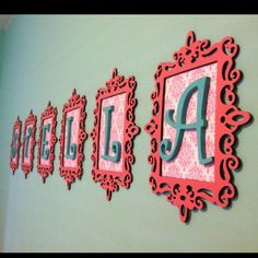 $1 wooden frames spray-painted pink, girly scrapbook paper, and painted wooden letters from the craft store. So pretty for the girls room!: