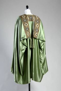 (1904) Cape of light green silk satin lined with white satin. Trimmed with bands of wool and silk thread embroidery in blue, green, and light brown at neckline and top edge. Two large ornamental gold colored buttons with black and white design of birds and tree branches. Green silk frog attached to one of the buttons. Green silk tassel trim at back.