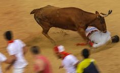 A reveller is pushed on the ground at the San Fermin Festival, in Pamplona, Spain.