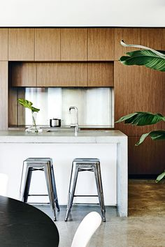 concrete waterfall edge + wood cabinetry + tolix stools