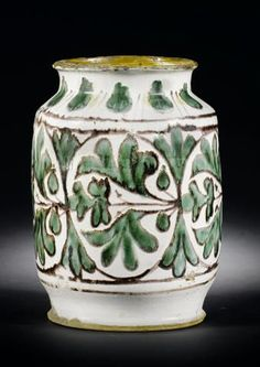 30.000€-1475-An extremely rare early Florentine maiolica albarello.  second quarter 15th century Painted in green outlined in manganese with a broad band of scrolling foliage around the centre between manganese line borders, the neck with a band of leaves alternating with two dashes, 22.5cm high