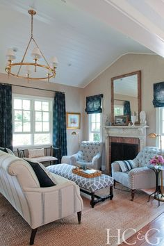 The hand-carved mantel from Black Swan Antiques was cut to fit the living room's petite proportions. The window treatments, wall covering and chairs are from Ralph Lauren Home; the sofa and bench are from English Country Antiques.