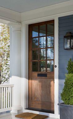 Grayish blue siding, white trim, light blue ceiling, and dark brown wood door. via anne decker architects.