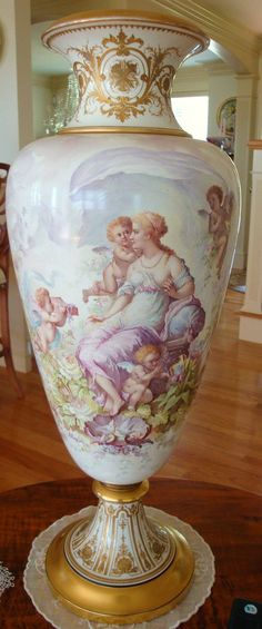 Servres Bolted Palace Porcelain Hand Painted Vase With Cherubs, Lilacs And Roses Painted Against A Pale Cream Background And With Gold Trim, Signed By The Artist    c. Mid 1800's